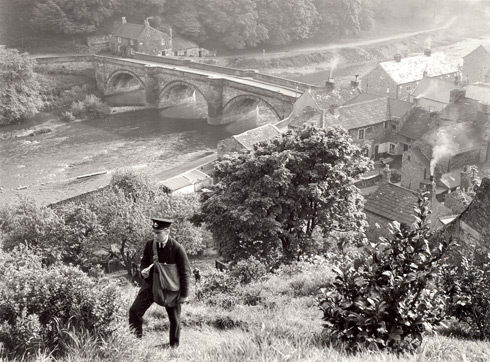 A postman walking alongside the River Swale near Richmond, Yorkshire, 1938.