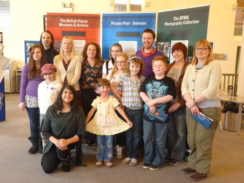Participants in Picture Post Swindon pose in front of the display.