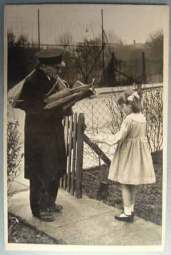 A little girl receives a copy of a Braille book through the post from the National Library for the Blind, now part of RNIB.