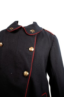 A Postwoman's overcoat, 1918. The coat is dark blue with red detailing on the edges, gold buttons and T5 in gold on the collar.
