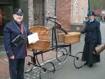 Colin and Maragret Bedford dressed as a Victorian postman and postwoman, with the Hen & Chicks pentacycle.