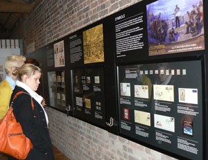 Visitors viewing the display Post Abolition: Commemorative stamps from around the world at Museum of London Docklands