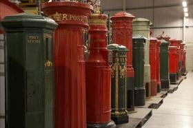Pillar boxes arranged in a line at the British Postal Museum Store