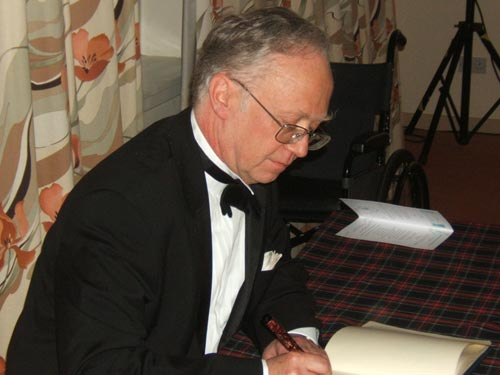 Douglas Muir signs the Book of Scottish Philatelists
