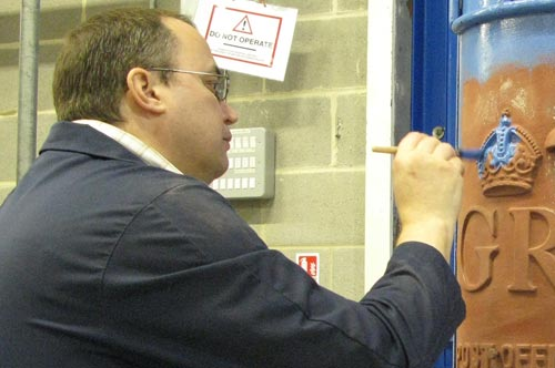 Julian Stray applies blue undercoat to some of the 'fine work' of the prepared pillar box
