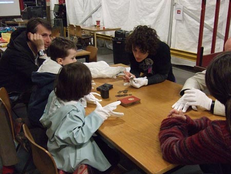Family visitors investigating parts of the handling collection with a white glove session
