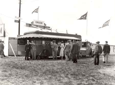 Customers queue to use the Mobile Post Office which is situated in the grounds of an agricultural show in West Sussex, 1938.