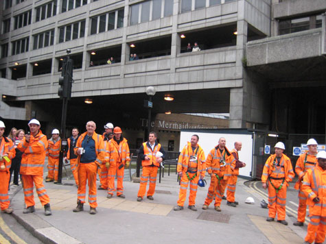 Workers take a break from building Crossrail to watch the parade.