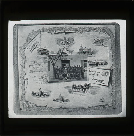 A black and white lantern slide of an image of a map, with a group photo in front of Field Post Office in the centre.