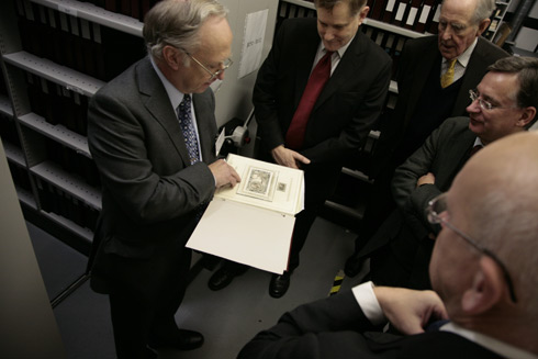 Curator of Philately Douglas Muir shows the group some stamp artwork.
