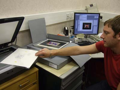 Stuart from the Cataloguing team scans unadopted artwork from the 1994 Greetings stamps