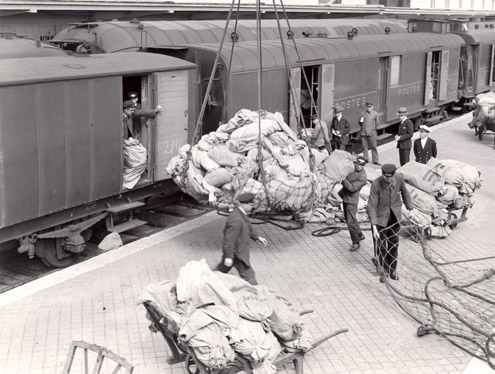 Staff load mail into large cargo nets at the platform of Calais Station.