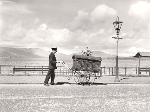 A postman pushes a hand cart with a large GPO basket on it along a promenade, Greenock.