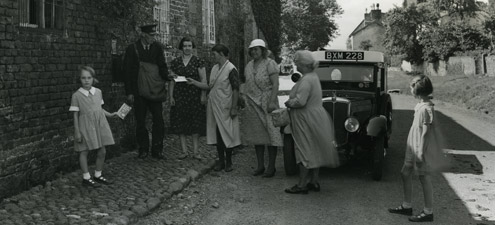 Postman driver collecting at Shotwick, Cheshire. Women and children queueing in the street to hand over mail. (POST 118/1866)
