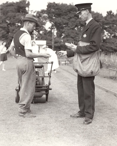 A postman delivers mail at Gorleston-on-Sea holiday camp. He hands a letter to an employee at the camp. (POST 118/679)