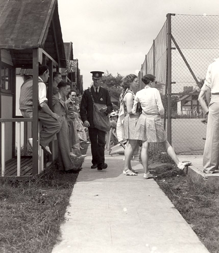 A postman delivering mail at Hemsby holiday camp. (POST 118/681)