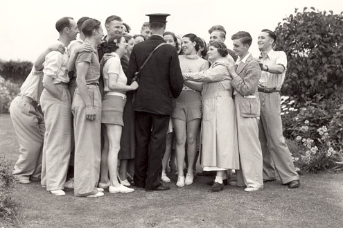 A postman delivers mail to a large group of people at Caister holiday camp. (POST 118/683)