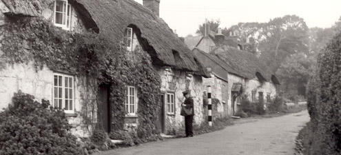 A postman delivers mail to cottages in North Street in Brighstone, Isle of Wight, 1937.