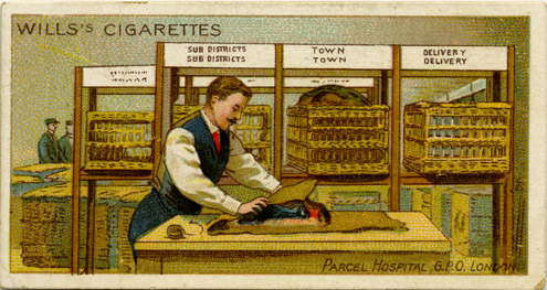 "Front of Wills' cigarette card number 28 showing a parcel hospital at G.P.O., London, c. 1911-1936 (2010-0383/28). The back of the card reads ""In every large post office provision is made for the repacking of parcels which have suffered damage in transit, in almost every case the result of insufficient packing. When the damage is limited to the packing paper being torn, repair is easy, but articles are sometimes so smashed or broken that compensation, not exceeding £2, is voluntarily given""."