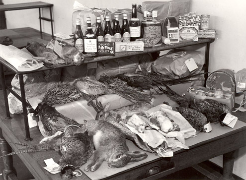 Mount Pleasant Parcel Office - Returned Parcels Section, 1938. Items found in the Returned Parcels Section are displayed on a table. Items include dead animals and birds, bottles of beer and various foodstuffs. (POST 118/939)