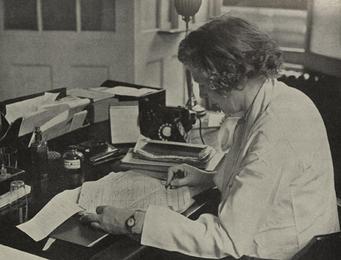 Female doctor examining medical reports at Post Office Headquarters (Green Paper 31 - the Post Office Medical Service, POST 92)