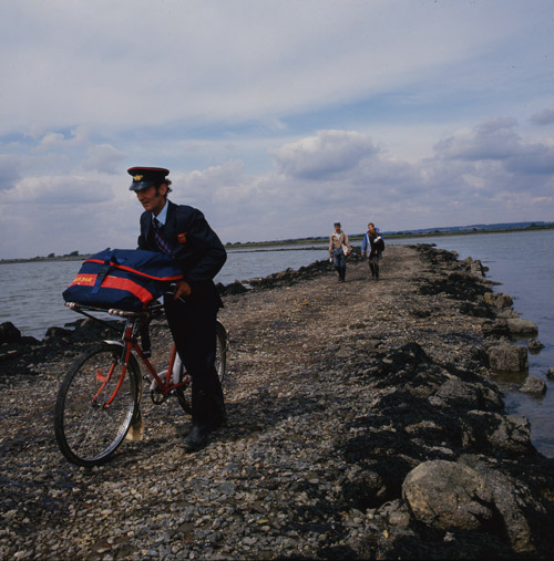 A postman pushes his bicycle across a causeway while delivering mail to Osea Island, Maldon, Essex, 1987. (003-012-001)