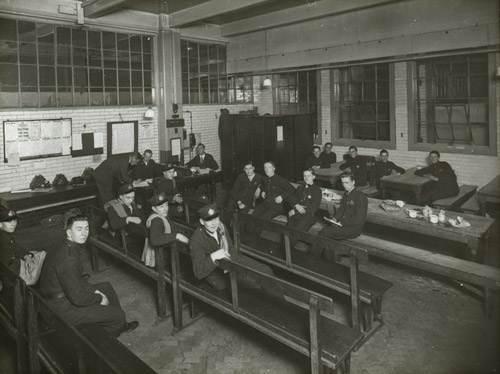 A group of telegram messenger boys sat in rows on wooden benches in the L.P.S. Boy Messengers Retiring Room, c. 1930-40 (2012-0049/05)