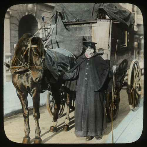 A hand-coloured photographic lantern slide of a parcel postwoman standing beside the horse of the horse-drawn mail coach, Germany. (2012-0030/02)