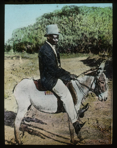 A hand-coloured photographic lantern slide of a rural postman in Dominica, British West Indies, wearing a light blue top hat, white trousers and a blue jacket whilst riding a white donkey. (2012-0030/16)