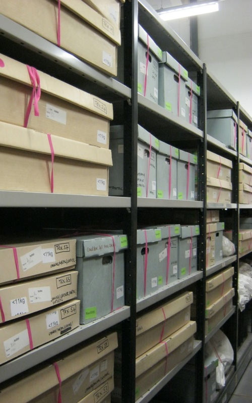 A view from inside the mobile shelving, showing shelves containing audited objects with lots of lovely pink tape….