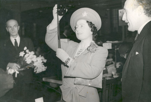 Queen Elizabeth taking a look at an airgraph film. The Queen sent the first airgraph to launch the service in 1941.