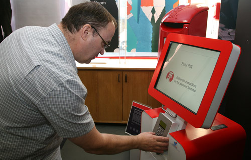 Curator, Julian Stray, using the Royal Mail's Post and Go machine, newly installed in the foyer of the British Postal Museum & Archive.