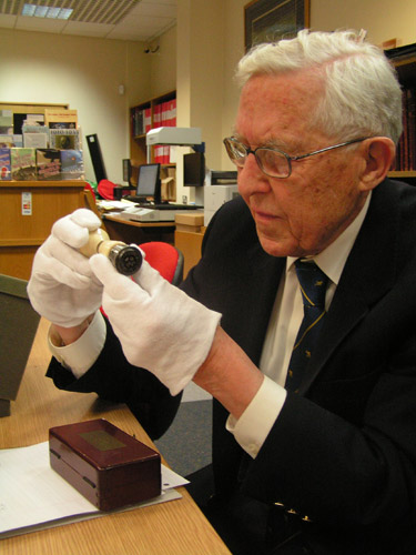 John Crowe examines the handstamp during his visit to the Royal Mail Archive.