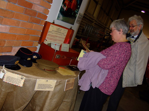 Two visitors explore the suitcase, and share their memories of the 'Save for Victory' campaign. This public appeal encouraged people to save for the war effort.