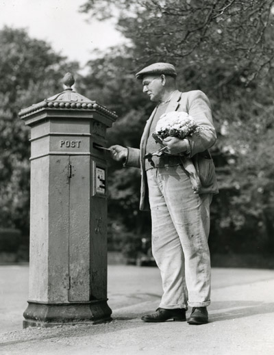 Man posting a letter holding a cauliflower, 1949. (POST 118/1964)