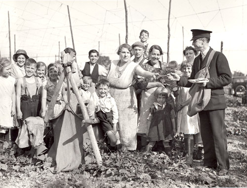 Postman delivering mail to a large group of hop pickers, Kent, 1935. (POST 118/467)