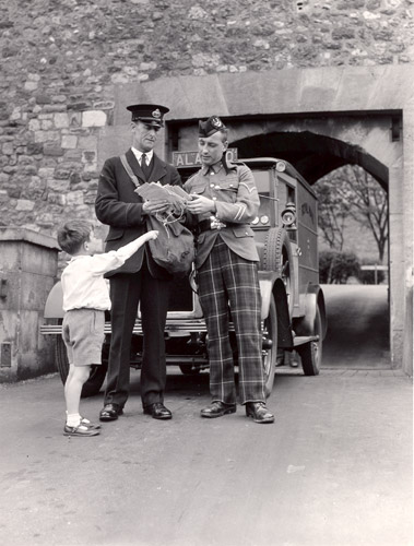 Postman delivering mail to Dover Castle. The postman, standing in front of his mail van, hands mail to a soilder. A young boy stands next to the men, pointing at the postmans mail bag. 1935. (POST 118/421)