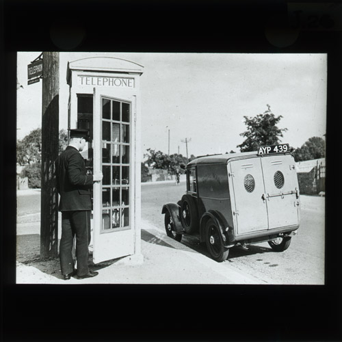 Lantern slide with postman, kiosk and sign. (2011-0443/6)