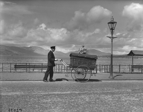 A postman pushes a hand cart with a large GPO basket on it along a promenade, 1938. The basket contains mail unloaded from the Canadian Pacific Railways liner Duchess of Bedford at Greenock. Beginning its journey in places such as New Zealand and China, once unloaded, the mail was then sorted in the open air 'sorting office' of the Princes Pier before being despatched for delivery across the United Kingdom. (POST 118/851)