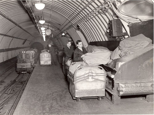 Postmen loading bags from conveyor into containers to use on the Post Office underground railway. (POST 118/381)
