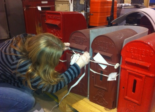 Curator Emma measures the lamp boxes