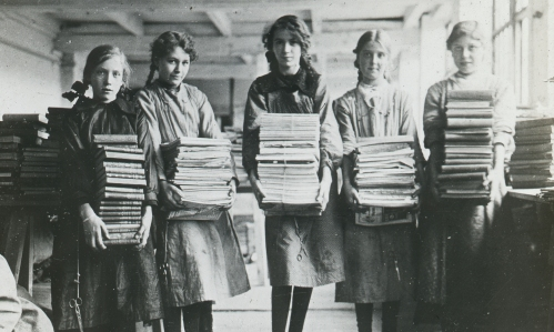 A black and white photographic lantern slide of a group of five girls holding stacks of newspapers, magazines and books.