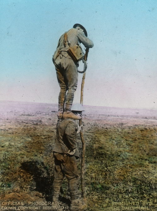 Human Ladder For Telephone'. Two men in uniform, one standing on the other's shoulders.