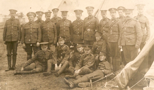 Photograph of Sergeant Thomas May (second from left on front row) of the Post Office Rifles with the rest of his company outside some tents. (2013-0021/3)