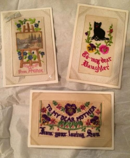 Three of the embroidered cards on display.