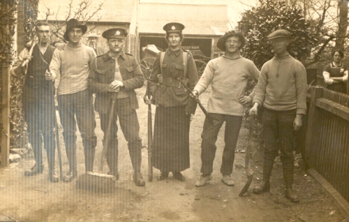 Photograph of six people holding brooms and rifles. PORs changed into this when they were cleaning their uniform. Thomas May is third from left.