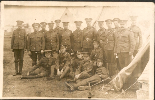 Photograph of Sergeant Thomas May (second from left on front row) with the rest of his company outside some tents.